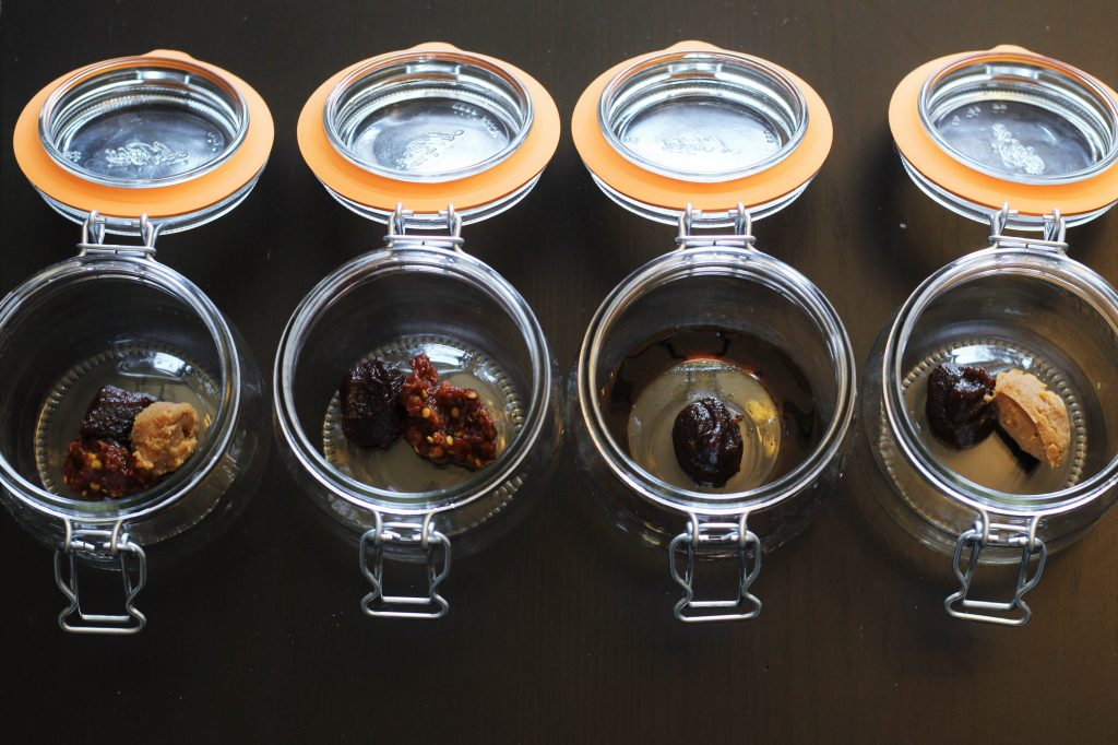 """four glass containers with various """"soup bases"""" and """"flavor boosts"""""""