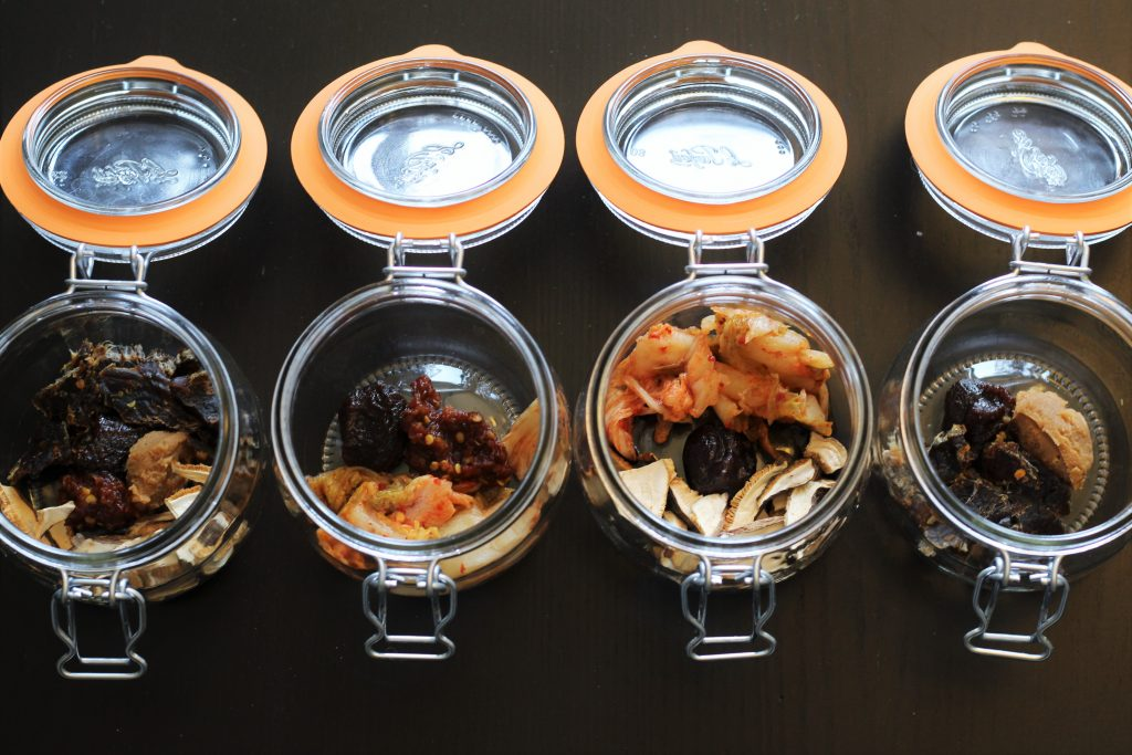 The four glass jars with various vegetables and jerky added.