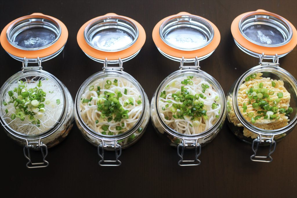 The four glass jars with various noodles added.