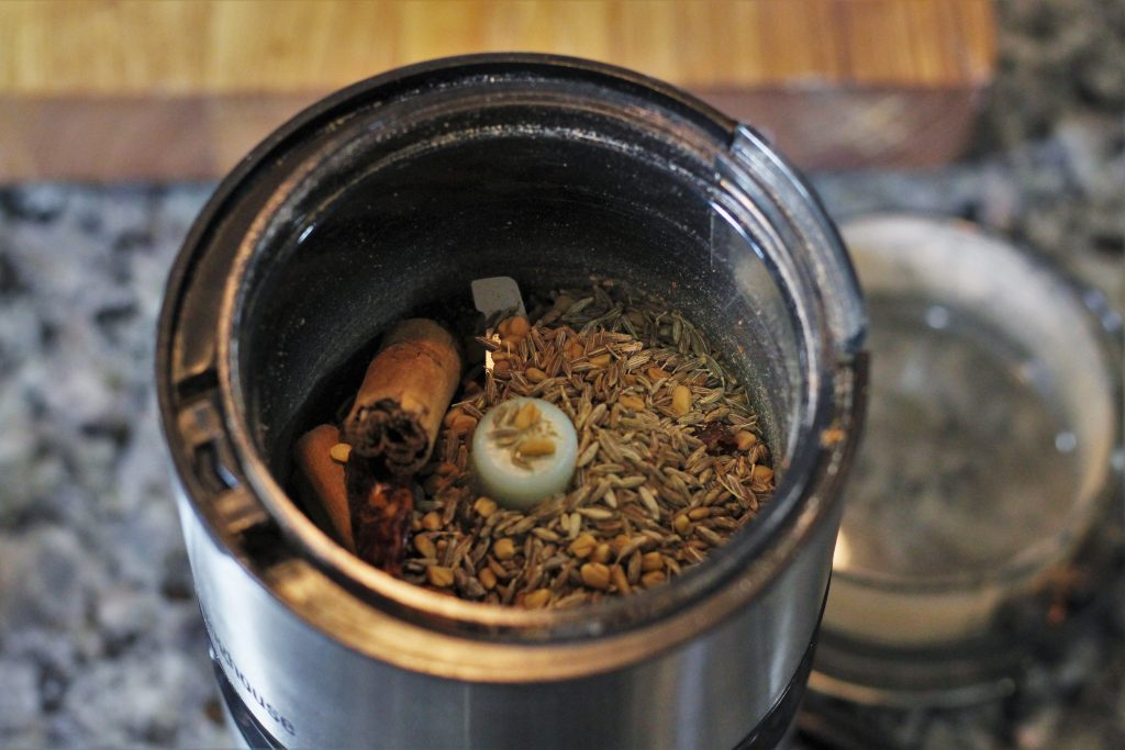 the ingredients of the curry powder in a spice grinder