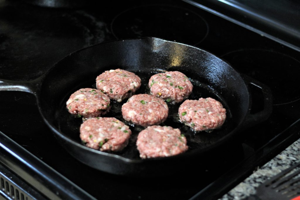7 patties in a cast iron skillet being cooked.