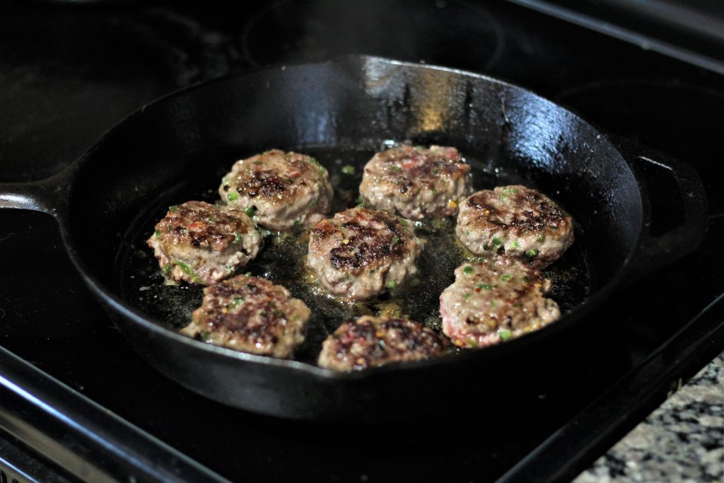 8 patties in a cast iron skillet being cooked.