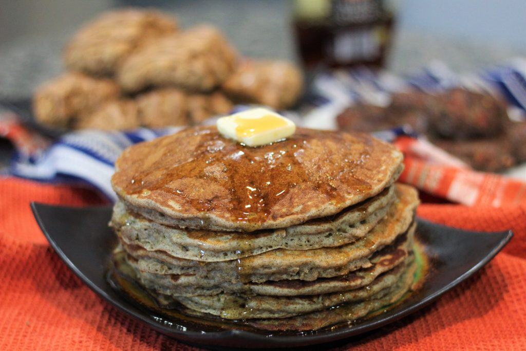 A stack of pancakes with butter and maple syrup.