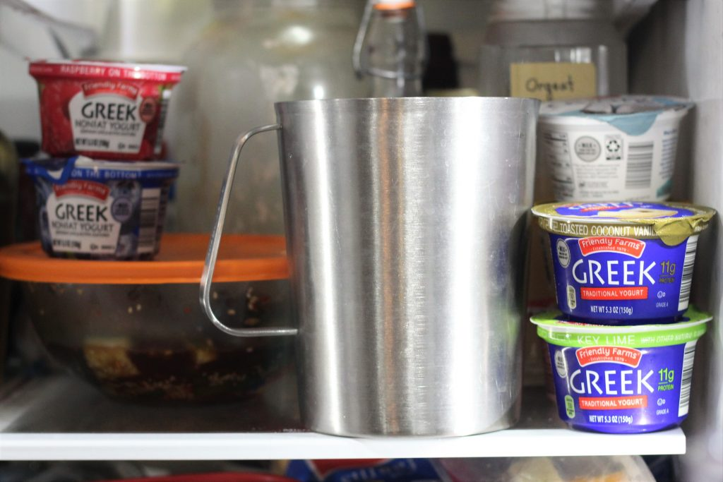 The metal pitcher on a shelf in a fridge.