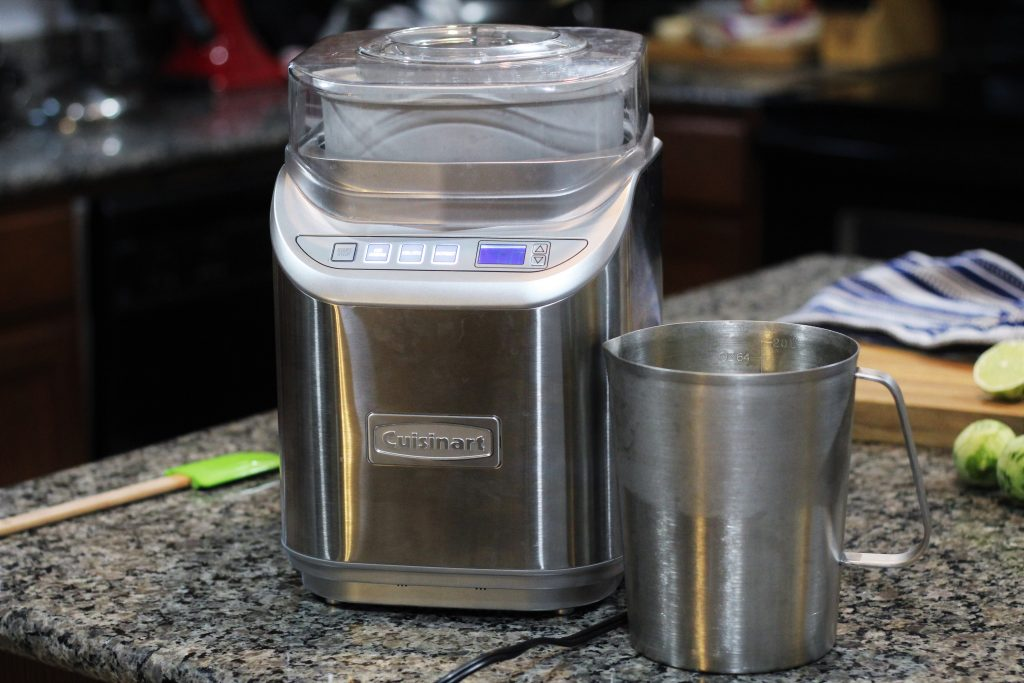 A Cuisinart ice cream machine on a counter with the metal pitcher beside it.