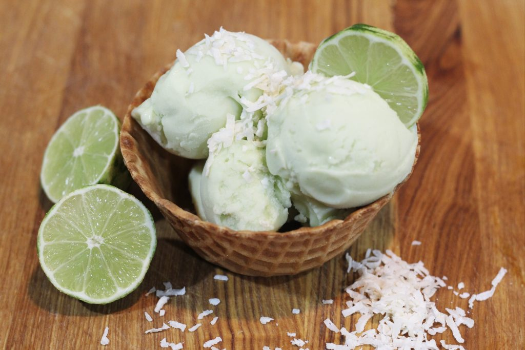 Waffle cone bowl with scoops of lime ice cream topped with coconut flakes and a lime slice.