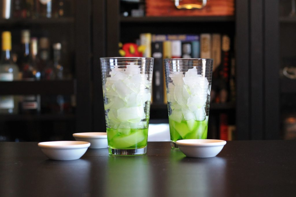 Two tall glasses filled with ice cubes, each with a small amount of melon liqueur at the bottom.
