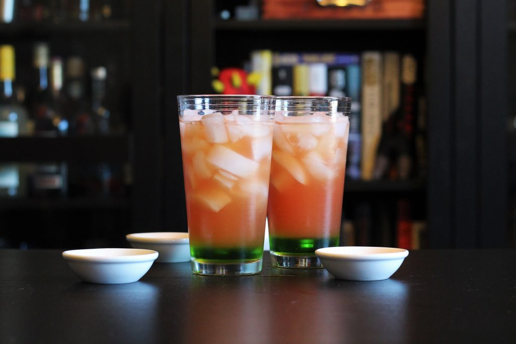 Two tall glasses filled with ice cubes, each with a small amount of melon liqueur at the bottom, and the watermelon mix on top.