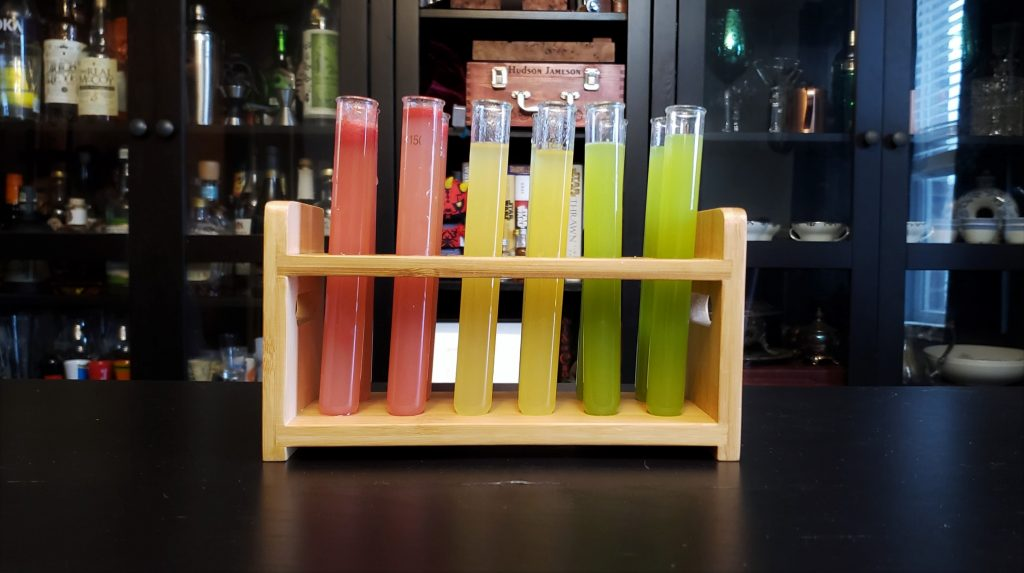 A rack of test tubes in 2 rows of 6. The first 2 by 2 section are pink, the next section are yellow, and the final section are green.
