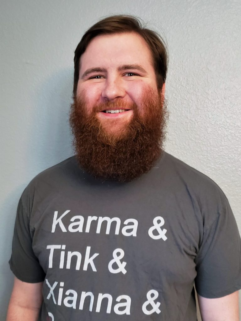 "Photo of Hudson. He is a white man, and is smiling and wearing a Tabletop Squadron shirt that says ""Karma & TInk & Xianna & Sabos"" with a red line through Sabos.  He has short brown hair, and a large auburn beard."