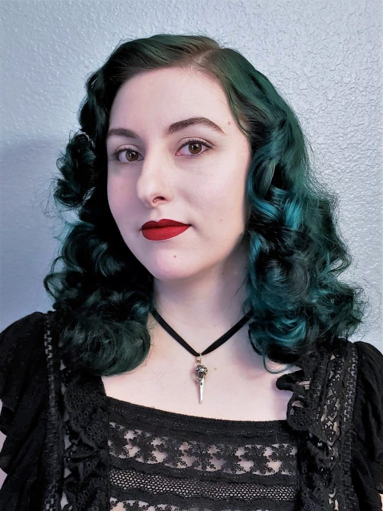 A photo of Laura. They are a white nonbinary person with dark teal hair that is curled in a vintage style. They are wearing a black top and small bird skull necklace.