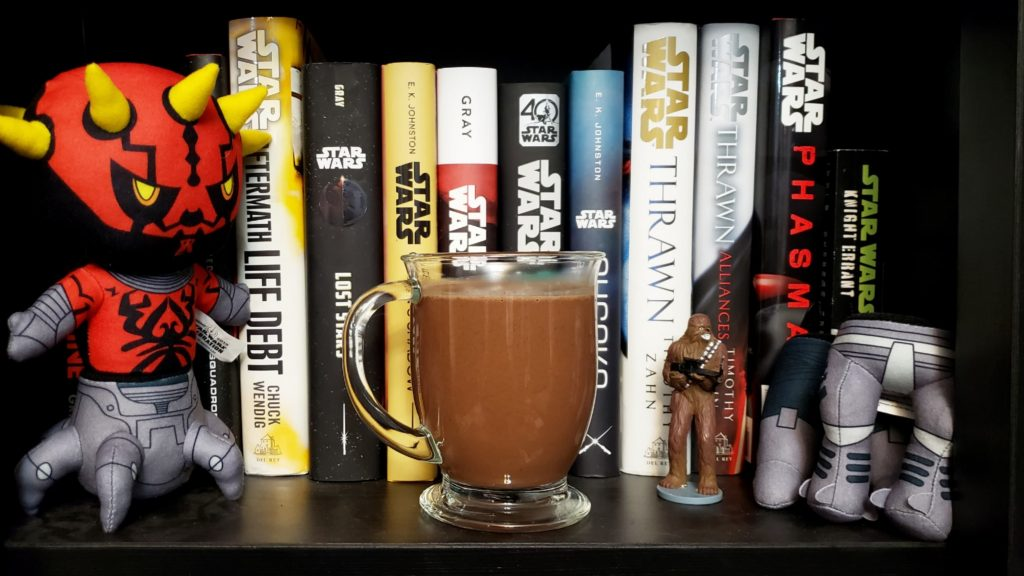 A clear mug of hot chocolate in front of Star Wars books on a shelf. To one side is a Darth Maul plushie, and on the other side is a small Chewbacca toy.