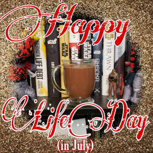 "A stylized image with a photo of mug of hot chocolate in the center. A glitter border surrounds it. Over layed is a large, fancy script saying ""Happy Life Day"", underneath is smaller, standard text saying ""(in July)"""